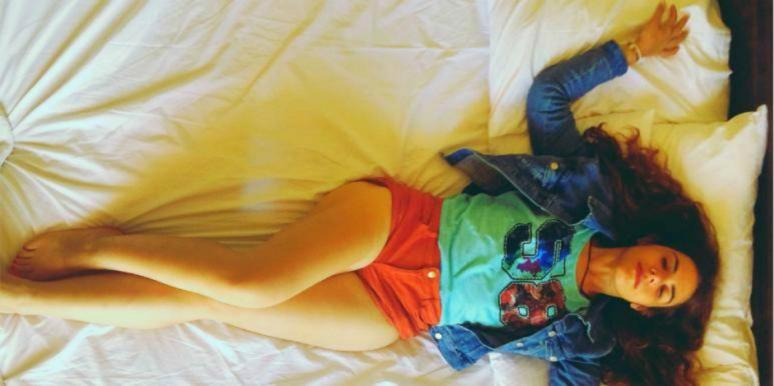 young woman with dark hair and orange shorts lies back on a bed