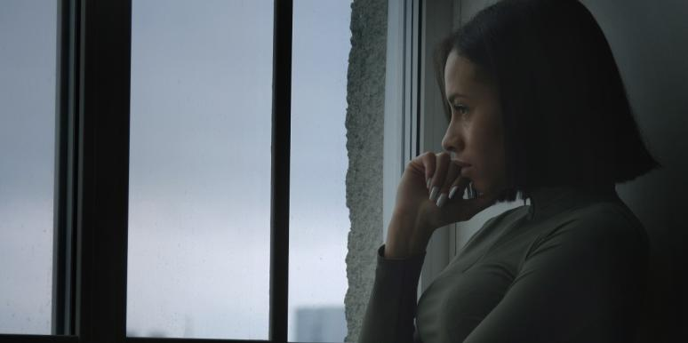 upset woman looking out a window