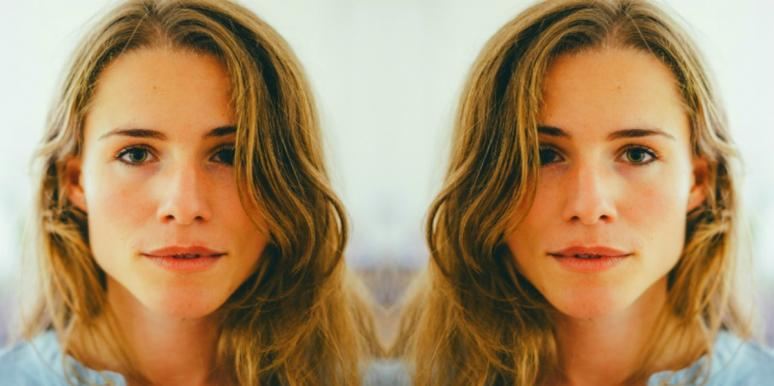 woman with long, wavy dark blonde hair looks into the camera in soft focus