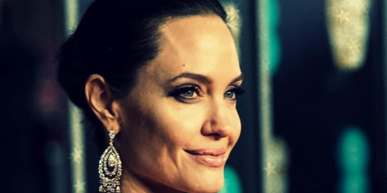 Angelina Jolie, hair pulled back in a bun, in a close-up from the right side, smiling slightly
