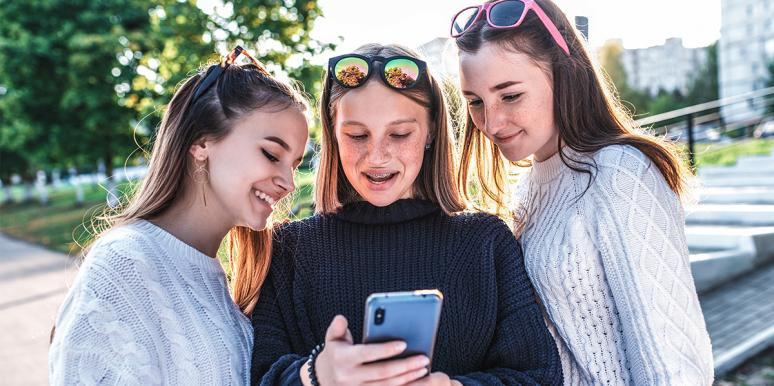 group of girlfriends looking at phone