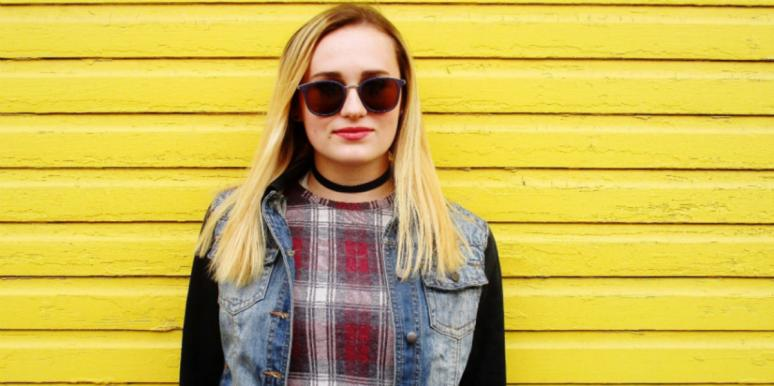 cool woman in sunglasses jean jacket smiling yellow background