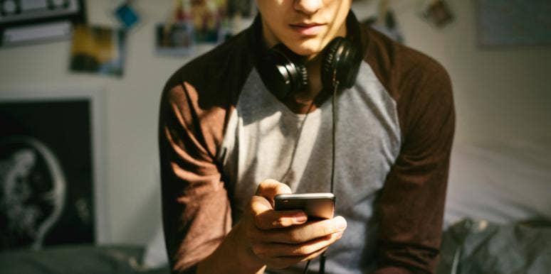 teen boy wearing headphones looks at his phone