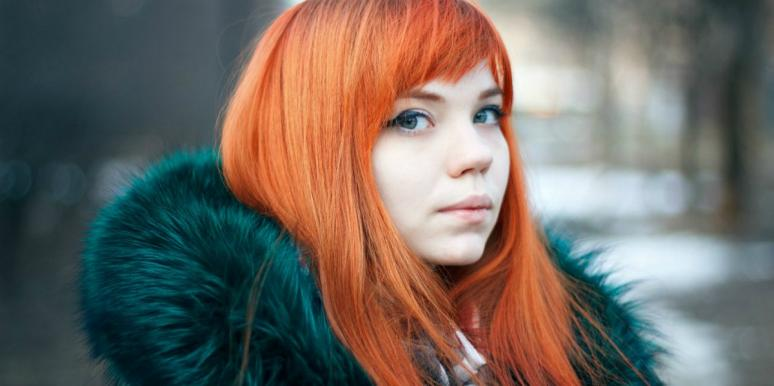 young woman with very pale skin and bright red hair looks sideways at the camera in a green faux fur jacket