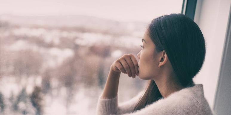 woman looking out window at cityscape