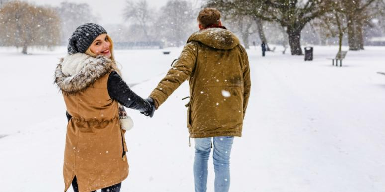 man and woman holding hands in the snow
