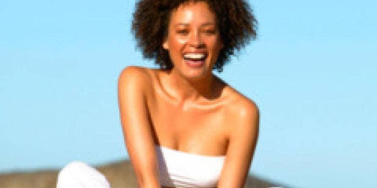 woman laughing sitting cross-legged outdoors