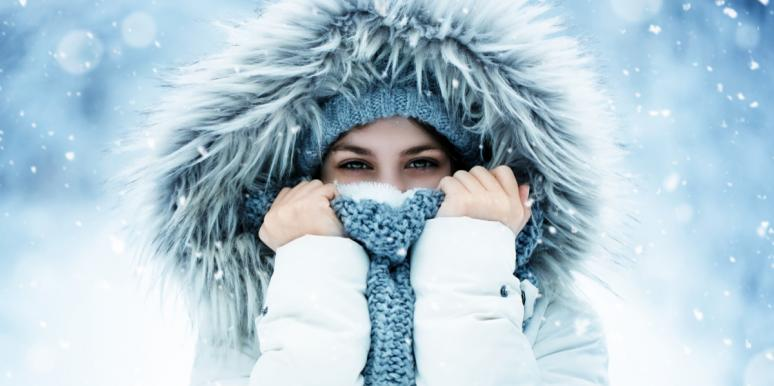 woman stands in the snow wearing a fur hood and covering her face