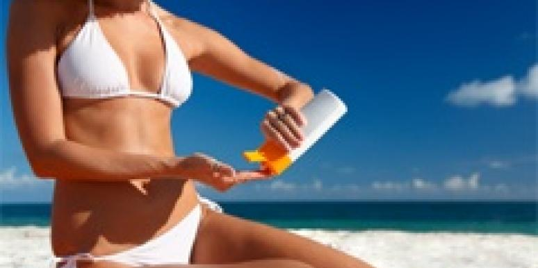 woman bikini applying lotion beach