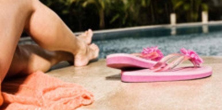 woman poolside lounging flip flops legs