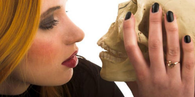 woman kissing skull