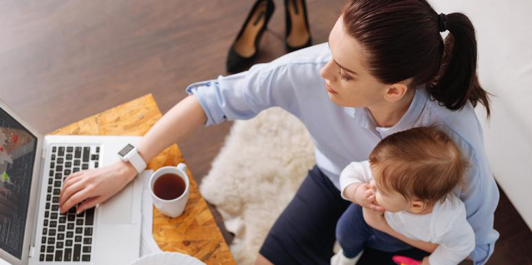 woman working at laptop with toddler on lap