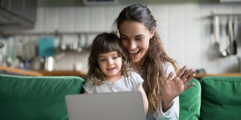 mom waving at computer with daughter on her lap
