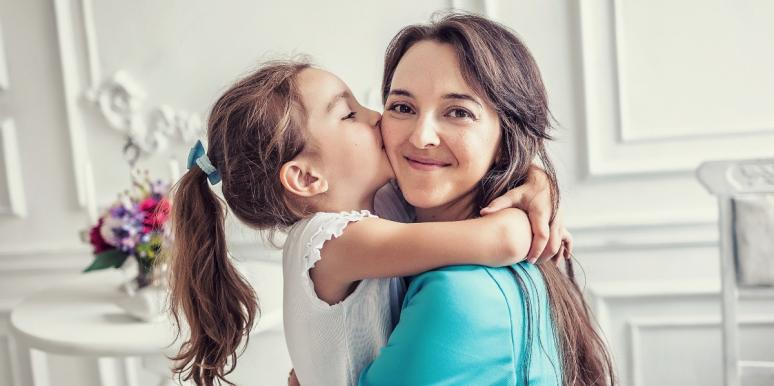 Daughter kissing smiling mom