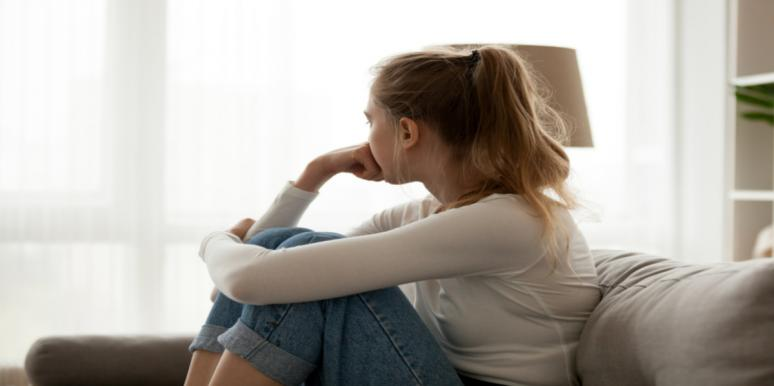 woman upset looking out window