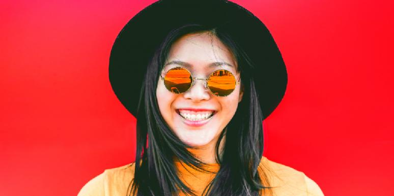 woman wearing sunglasses and smiling with a red background