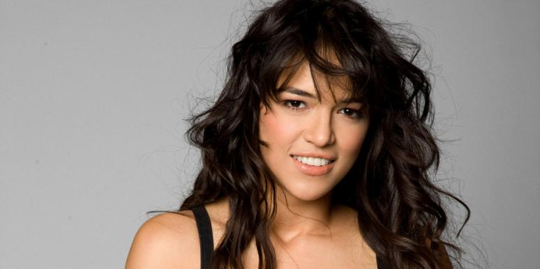 Proud and open bisexual Michelle Rodriguez, who is no longer dating neither Cara Delevingne nor Zac Efron, poses for a photoshoot with curly dark brown hair, natural looking makeup and a black tanktop in front of a slate gray background