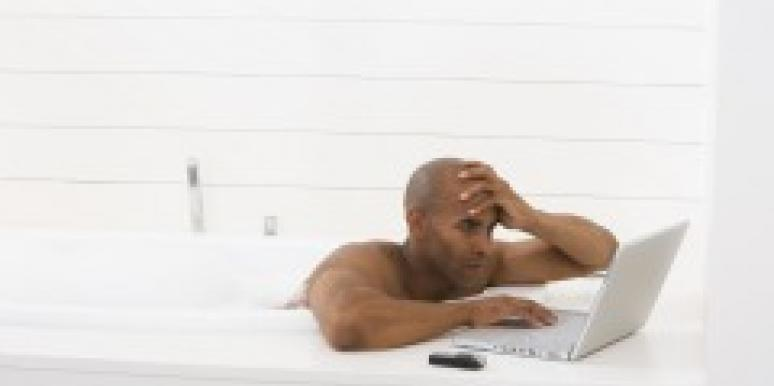 Man in bathtub with laptop
