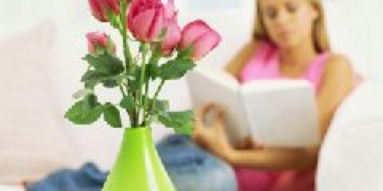 woman reading with roses in foreground