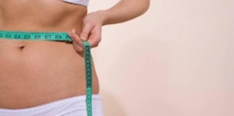 A woman measures her waist.