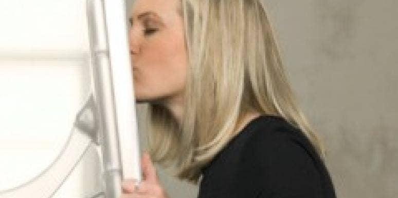 Woman kissing computer