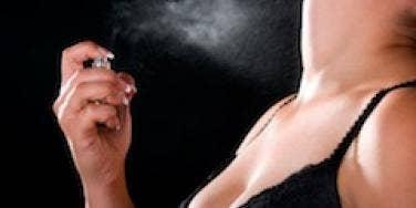 A sexy woman sprays perfume.