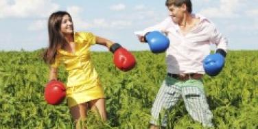 Couple in a field wearing boxing gloves