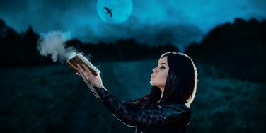 woman holding book under moon