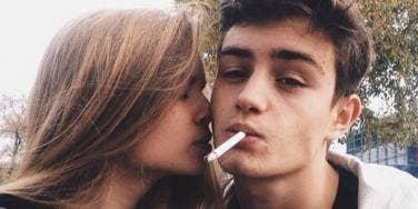 Guy smoking, girl kissing him