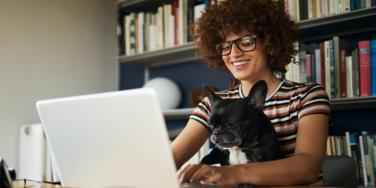 woman in glasses working at computer with French bulldog on lap