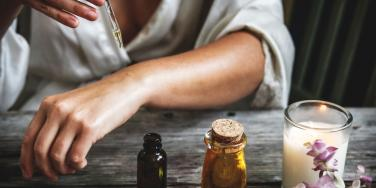 woman putting oil tincture on arm