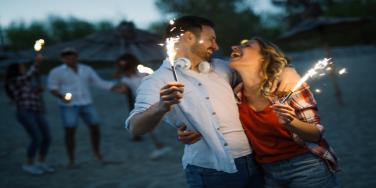 couple on the beach with sparklers for 4th of july date
