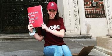 Abigail Mack wearing some Harvard merch and posing with an acceptance folder from the university.