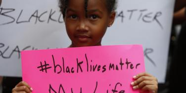 Black child holding a Black Lives Matter sign