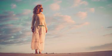 beautiful aging woman with curly brown hair stands on sand in front of vibrant sky