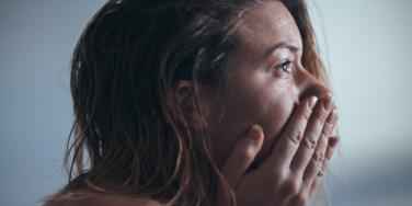 sad woman looking forward hands over face