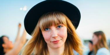 woman in black hat blond hair smiling