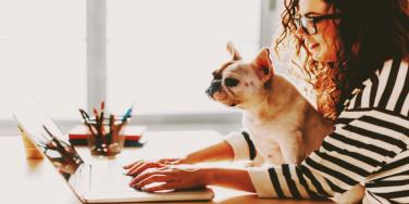woman working at computer with dog