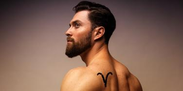 man with aries tattoo on shoulder