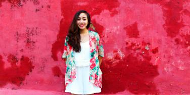 woman in floral shirt standing in front of red wall