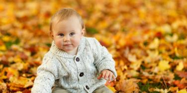 Baby boy sitting in leaves