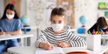 girl wearing mask in classroom