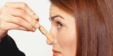 woman clipping clothes-pin to nose