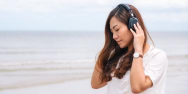 woman listening to headphones on beach