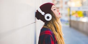 woman with headphones against wall