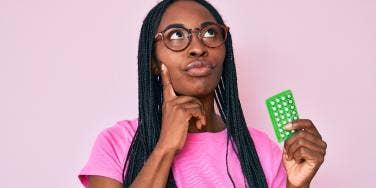 contemplative woman holding birth control pills