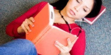 woman reading book lying down