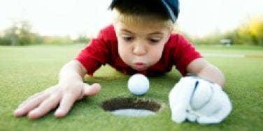 boy cheating golf ball