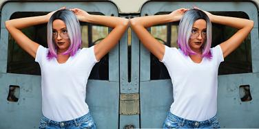 young woman with colorful hair in front of a train, pondering chaotic relationships