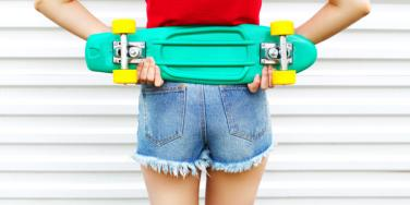 woman in jean shorts holding skateboard behind back